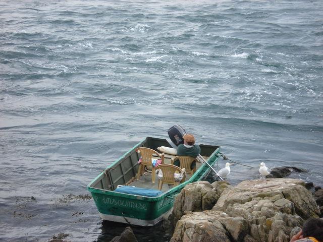 Petite barque à moteur avec des chaises en plastique dedans et appelée l'Insoumise