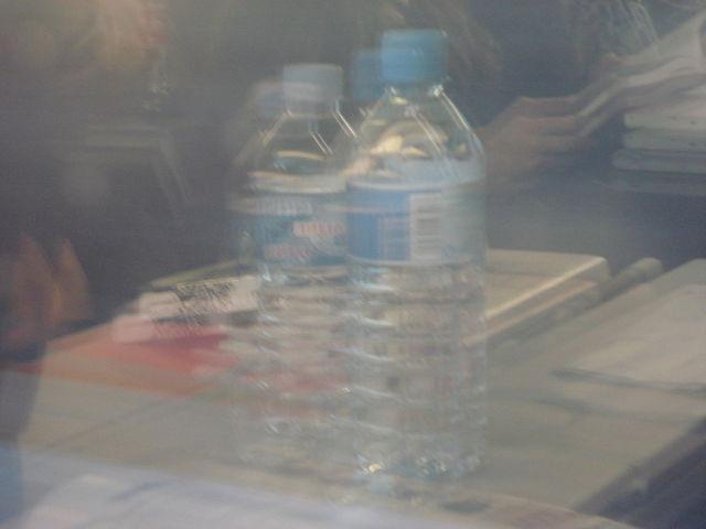Reflet de deux bouteilles d'eau dans la vitre d'un train, ce qui les fait paraître brouillées